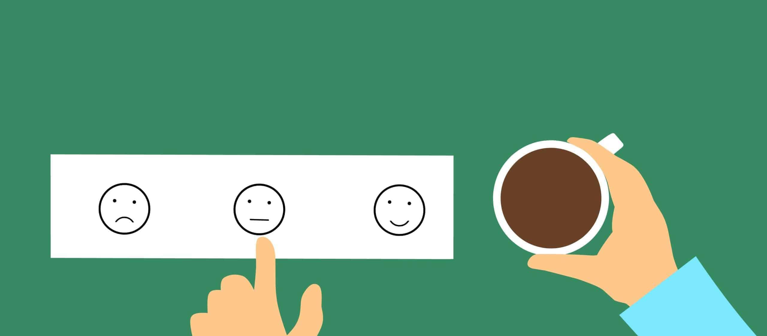 Online-Vertriebsberatung | Ein grüner Tisch. Auf dem ist ein weißer Zettel mit 3 Gesichtern. Lachen, emotionslos, traurig. Ein Mitarbeiter zeigt auf den mittleren Smilie als Sinnbild für die Mitarbeitermotivation